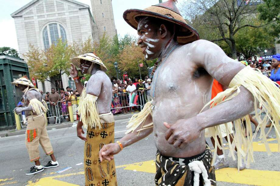 Emmanuel Pierre, right, and others make their way along Eastern Parkway in the Brooklyn borough of New York as they take part in the West Indian Day Parade Monday Sept. 1, 2014. Photo: Tina Fineberg, Associated Press / FR73987 AP