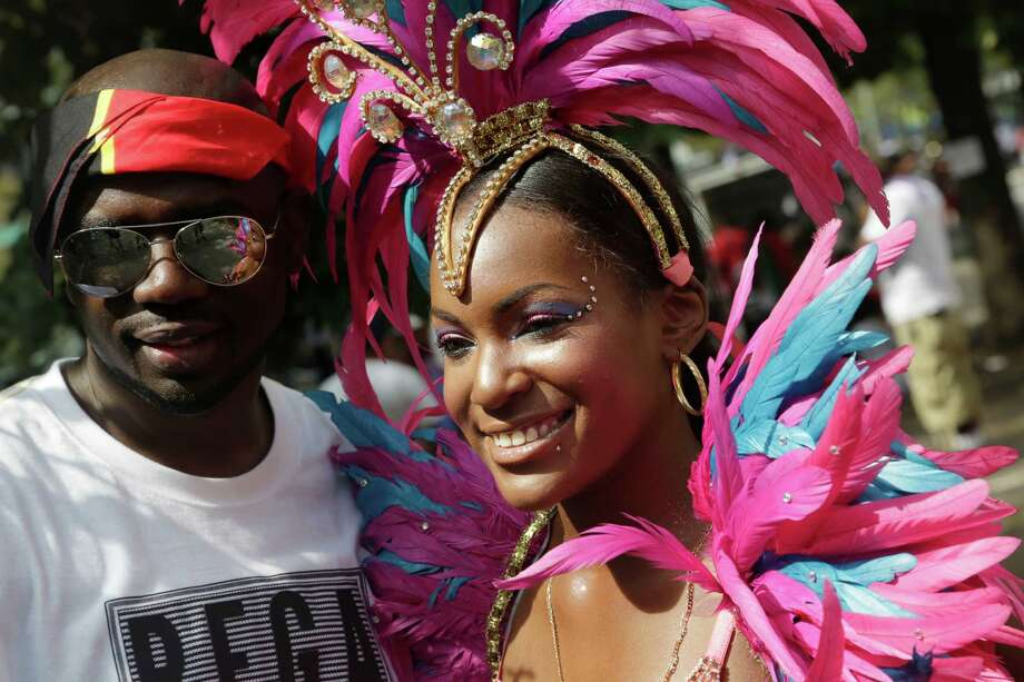 Brittany Grice, dressed to march in the West Indian Day Parade, poses for a photo with an unidentified admirer, Monday, Sept. 1, 2014, in the Brooklyn borough of New York.  Photo: Mark Lennihan, Associated Press / AP