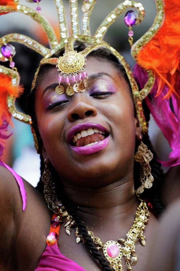 A dancer poses for a photograph during the West Indian Day Parade, Monday, Sept. 1, 2014 in the Brooklyn borough of New York. The annual parade draws about 1 million people along its 2-mile-long route.  Photo: Mark Lennihan, Associated Press / AP