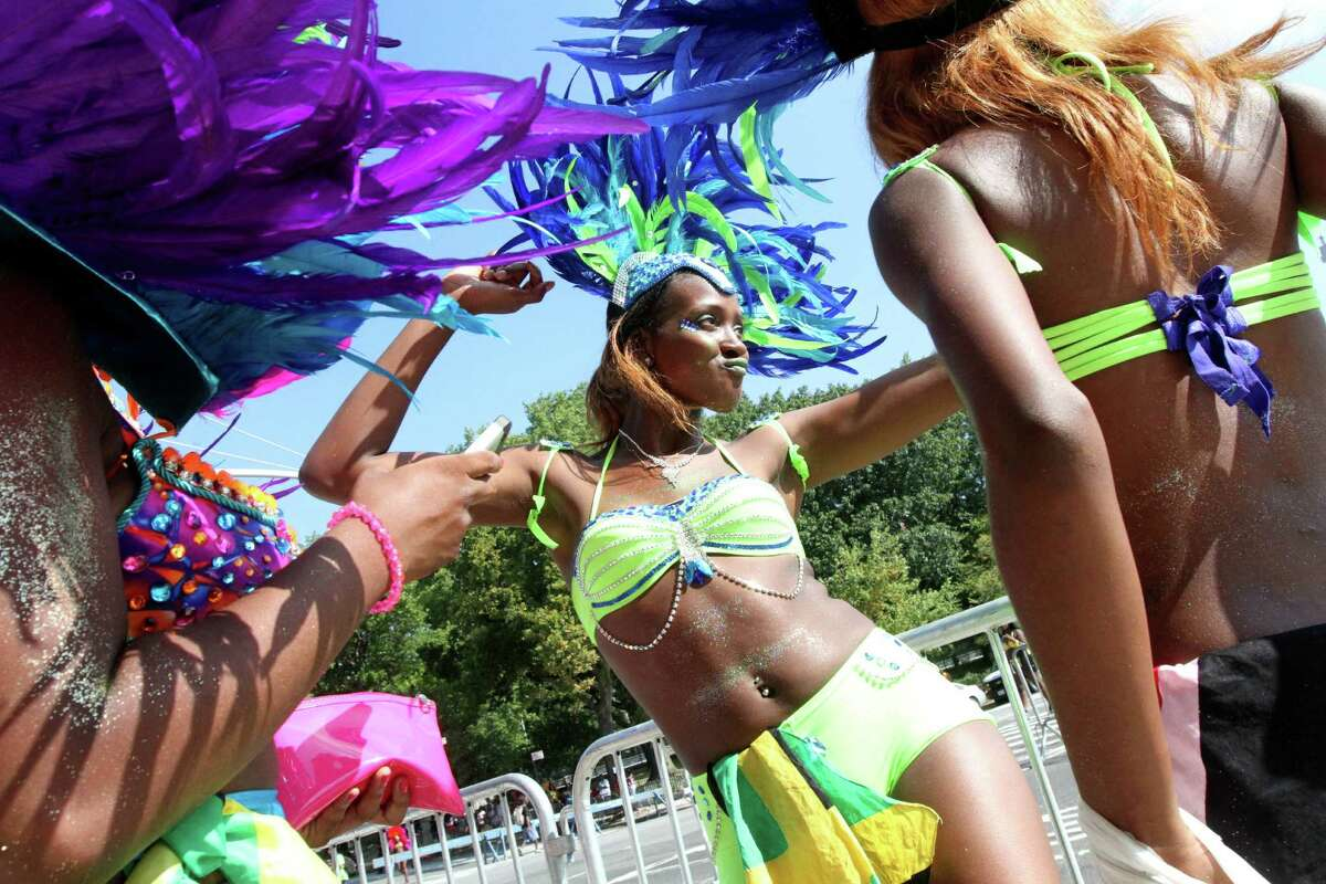 Dressed for the occasion, Adjee Hamilton, center, dances as she and others wait to take part in the West Indian Day Parade, Monday, Sept. 1, 2014 in the Brooklyn borough of New York.