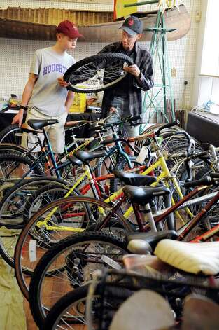Chris Denham, 15, of Glenville, left, and his father, Larry Denham, shop for used bike tires at the Electric City Bike Rescue on Thursday, Aug. 28, 2014, at Edison Technical Center in Schenectady, N.Y. (Cindy Schultz / Times Union) Photo: Cindy Schultz / 00028366A