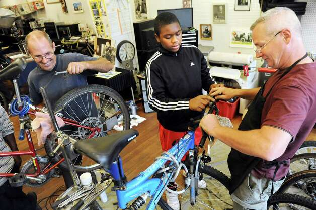 ElJastar Scott, 15, of Colonie, center, gets help with bike repairs from volunteer Dave Davis, right, as volunteer Rennie Fountain, left, assist another customer at the Electric City Bike Rescue on Thursday, Aug. 28, 2014, at Edison Technical Center in Schenectady, N.Y. (Cindy Schultz / Times Union) Photo: Cindy Schultz / 00028366A