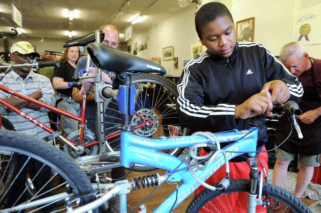 ElJastar Scott, 15, of Colonie, works on his bike at the Electric City Bike Rescue on Thursday, Aug. 28, 2014, at Edison Technical Center in Schenectady, N.Y. (Cindy Schultz / Times Union) Photo: Cindy Schultz / 00028366A