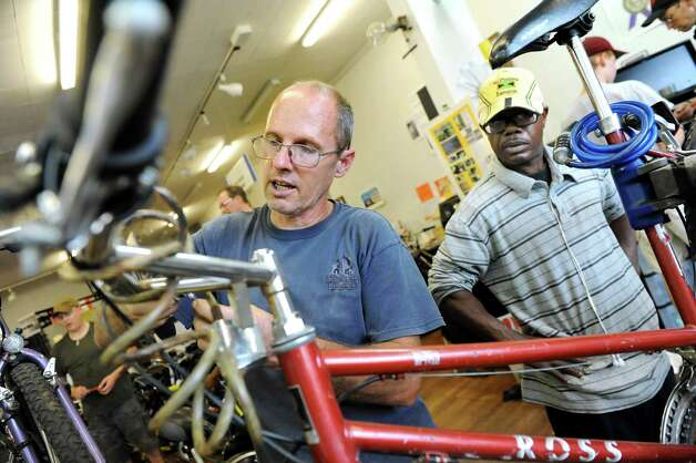 Volunteer Rennie Fountain, left, works on a bike for Norman James of Schenectady at the Electric City Bike Rescue on Thursday, Aug. 28, 2014, at Edison Technical Center in Schenectady, N.Y. (Cindy Schultz / Times Union) Photo: Cindy Schultz / 00028366A