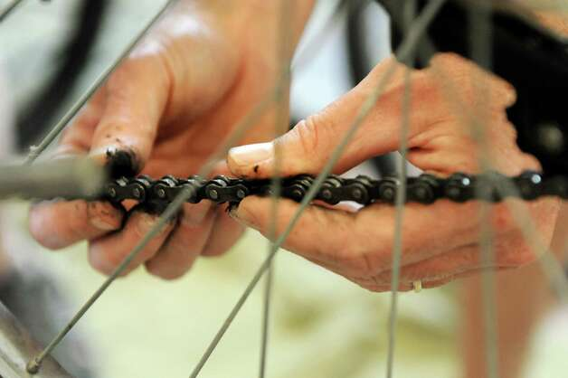Volunteer Rennie Fountain works on a bike chain at the Electric City Bike Rescue on Thursday, Aug. 28, 2014, at Edison Technical Center in Schenectady, N.Y. (Cindy Schultz / Times Union) Photo: Cindy Schultz / 00028366A