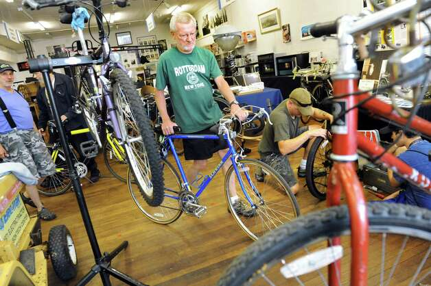 Volunteer Rich Vertigan, center, wheels in a bike that needs repairs at the Electric City Bike Rescue on Thursday, Aug. 28, 2014, at Edison Technical Center in Schenectady, N.Y. (Cindy Schultz / Times Union) Photo: Cindy Schultz / 00028366A