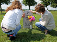 Michelle Campbell, left, stands beside her mother, Francesca, at the gravesite of the late Vietnam veteran Robert Cesare on Thursday, August 14, 2014 in Saratoga National Cemetery in Saratoga, N.Y.  Robert Cesare died from three different forms of cancer due to exposure from Agent Orange used during the Vietnam War.  (Tom Brenner/ Special to the Times Union)