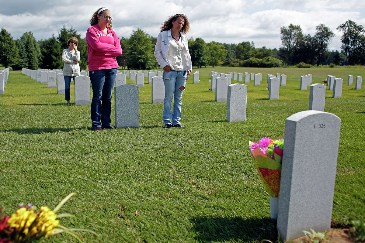 Francesca Cesare, back, and her granddaughter, Allie Campbell, left, and daughter, Michelle Campbell, right, stand at the gravesite of the late Vietnam veteran Robert Cesare on Thursday, August 14, 2014 in Saratoga National Cemetery in Saratoga, N.Y. Robert Cesare died from three different forms of cancer due to exposure from Agent Orange used during the Vietnam War. (Tom Brenner/ Special to the Times Union)