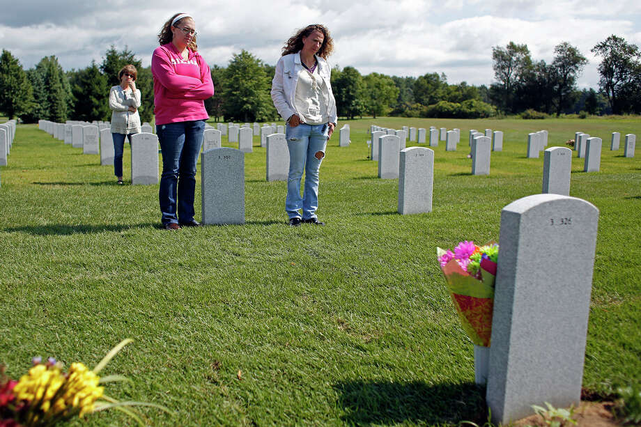 Francesca Cesare, back, and her granddaughter, Allie Campbell, left, and daughter, Michelle Campbell, right, stand at the gravesite of the late Vietnam veteran Robert Cesare on Thursday, August 14, 2014 in Saratoga National Cemetery in Saratoga, N.Y.  Robert Cesare died from three different forms of cancer due to exposure from Agent Orange used during the Vietnam War.  (Tom Brenner/ Special to the Times Union) Photo: Tom Brenner / ©Tom Brenner/ Albany Times Union