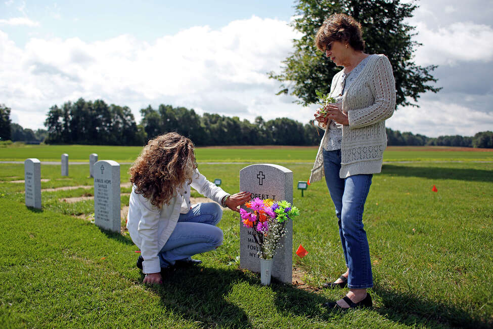 Michelle Campbell, left, mourns the death of her father, Robert Cesare, with her mother, Francesca Cesare, on Thursday, August 14, 2014 in Saratoga National Cemetery in Saratoga, N.Y. Robert Cesare died from three different forms of cancer due to exposure from Agent Orange used during the Vietnam War. (Tom Brenner/ Special to the Times Union)