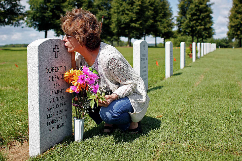 Francesca Cesare kisses her late husband's grave Thursday, Aug. 14, 2014, in Saratoga National Cemetery in Saratoga, N.Y. Robert Cesare died from three different forms of cancer due to exposure from Agent Orange used during the Vietnam War.(Tom Brenner/ Special to the Times Union)