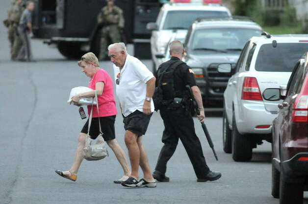 Saratoga County Sheriff officer guards neighbors as they evacuate during a standoff on Monday, Sept. 1, 2014, Waterford, N.Y. (Cindy Schultz / Times Union) Photo: Cindy Schultz