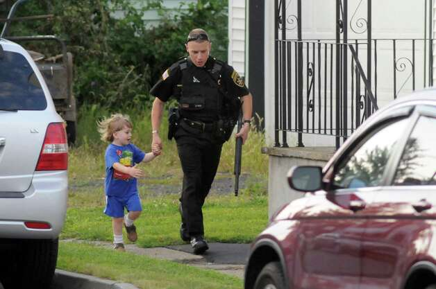 Saratoga County Sheriff officer runs with a child as he helps neighbors evacuate during a standoff on Monday, Sept. 1, 2014, Waterford, N.Y. (Cindy Schultz / Times Union) Photo: Cindy Schultz