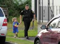 Saratoga County Sheriff officer runs with a child as he helps neighbors evacuate during a standoff on Monday, Sept. 1, 2014, Waterford, N.Y. (Cindy Schultz / Times Union)