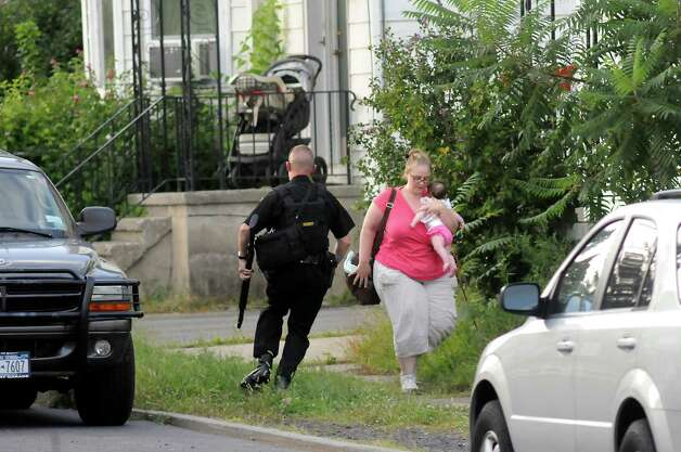 Saratoga County Sheriff officer guards a woman and her baby as he helps neighbors evacuate during a standoff on Monday, Sept. 1, 2014, Waterford, N.Y. (Cindy Schultz / Times Union) Photo: Cindy Schultz