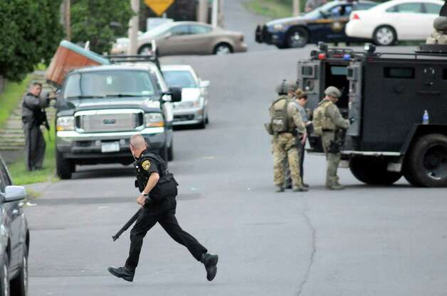 Saratoga County Sheriff officer runs into position during a standoff at at house on the corner of Grace Street and Vanderwerken Avenue on Monday, Sept. 1, 2014, Waterford, N.Y. (Cindy Schultz / Times Union) Photo: Cindy Schultz