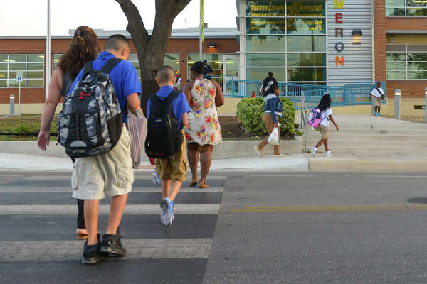 Students and parents head to the first day of classes at the re-opened Cameron Elementary Schoo. The school had been closed for two years and undergone $12 million in renovations.