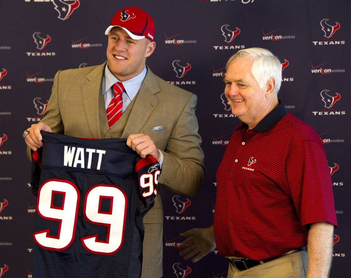 2011 Houston Texans first round draft pick J.J. Watt, a defensive end from Wisconsin, smiles as he holds his new Texans jersey while standing with defensive coordinator Wade Phillips during a news conference at Reliant Stadium Friday, April 29, 2011, in Houston. Watt was chosen by the Texans as the 11th pick in the first round of the NFL draft. ( Brett Coomer / Houston Chronicle )