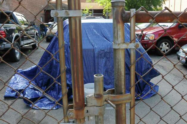 A vehicle hidden underneath a blue tarp, in a lot next to the Troy Police Department, appears to be the recovered SUV of murdered Lansingburgh man Al Lockrow on Monday, Sept. 1, 2014 in Troy, N.Y.  Police said they had found the vehicle on Friday, Aug. 29. Lockrow's wife, Maria, also was beaten to death. (Lori Van Buren / Times Union) Photo: Lori Van Buren