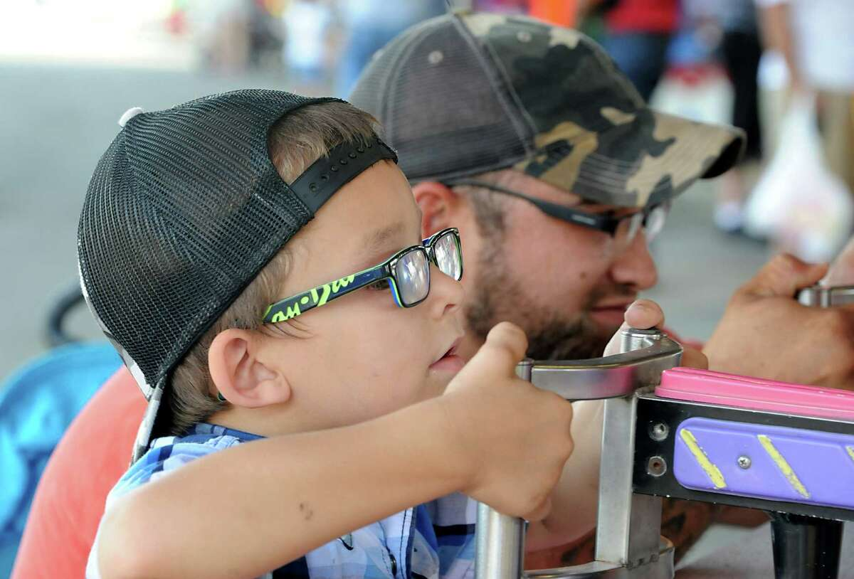 Cody Alessi, 4, of Stuyvesant, and his dad Mike Alessi play the Rising Waters spray racing game at the Columbia County Fair on Monday, Sept. 1, 2014 in Chatham, N.Y. (Lori Van Buren / Times Union)