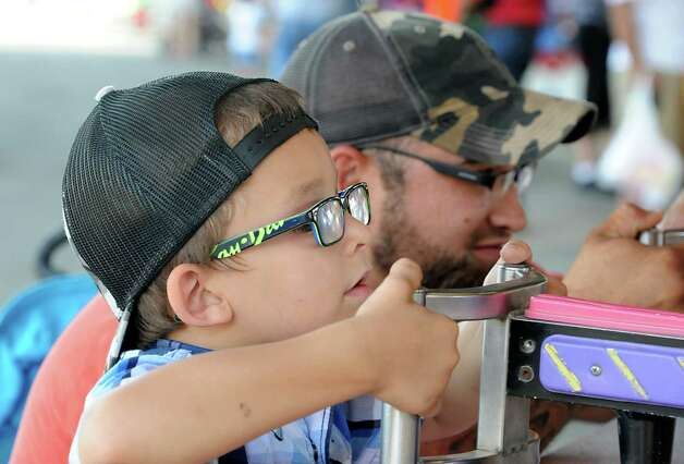 Cody Alessi, 4, of Stuyvesant, and his dad Mike Alessi play the Rising Waters spray racing game at the Columbia County Fair on Monday, Sept. 1, 2014 in Chatham, N.Y.  (Lori Van Buren / Times Union) Photo: Lori Van Buren / 00028266A