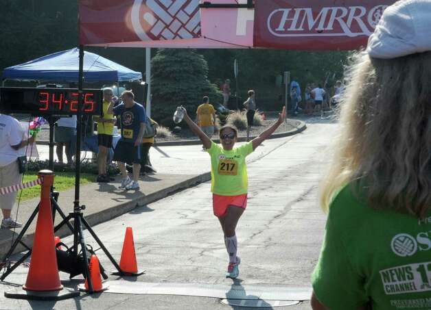 Divina McGuirk of Green Island throws her hands up in the air after finishing the SEFCU Labor Day 5k Race on Monday, Sept. 1, 2014 in Albany, N.Y.  (Lori Van Buren / Times Union) Photo: Lori Van Buren / 00028402A