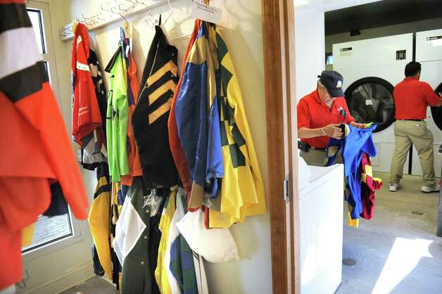 Colorman Walter Arce, center, cleans jockey silks before packing them on the final day of thoroughbred races on Monday, Sept. 1, 2014, at Saratoga Race Course in Saratoga Springs, N.Y. (Cindy Schultz / Times Union) Photo: Cindy Schultz, Albany Times Union / 00028394A
