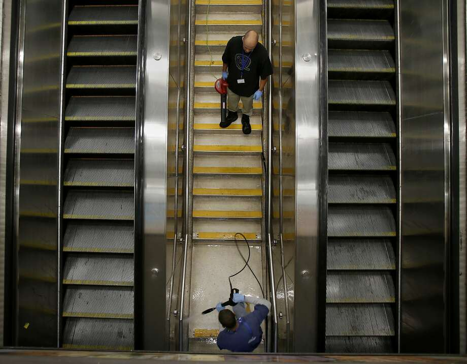 "A BART cleaning crew worked on a staircase between two escalators at the Powell Street station Sunday August 31, 2014. BART's traditionally dirty downtown San Francisco, Calif. stations are getting cleaned by a new ""brightening crew"" that is giving deep cleaning to station entrances, stairs, and other well used corridors. Photo: Brant Ward, The Chronicle"