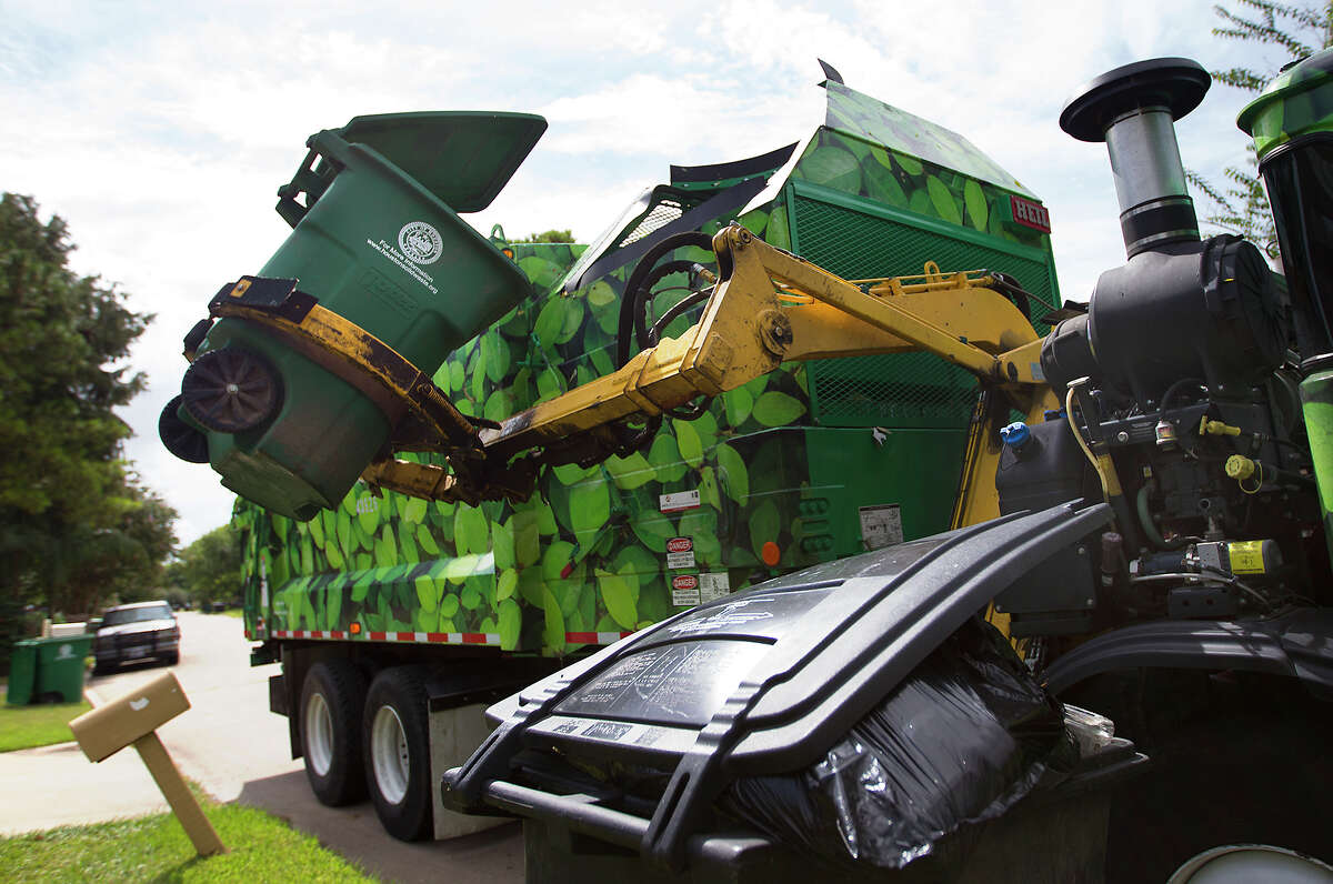 Ed Robinson picks up recycling along Woodmont Drive, Friday, Aug. 29, 2014, in Houston.