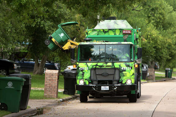 Ed Robinson picks up recycling along Windy Royal Drive, Friday, Aug. 29, 2014, in Houston. The proposal for One Bin, would replace the current method of separating out recyclables and trash into two bins, but rather into one. The trash would then be sorted and converted into materials at a state-of-the-art facility.