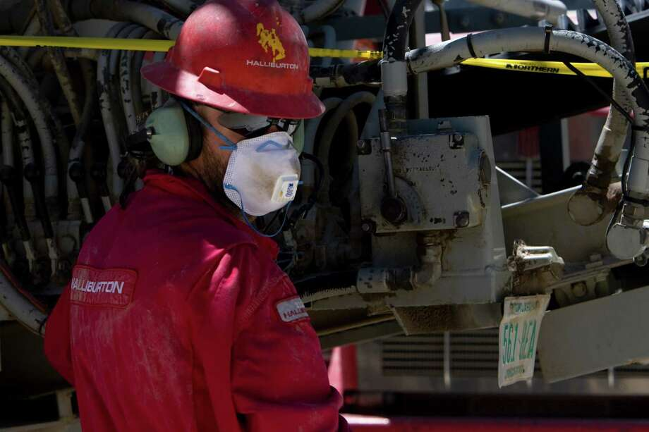 """A worker with Halliburton works on a well pad just after a charge was released in a well thousands of feet below creating multiple fractures in the cement-like crust that releases the """"tight gas"""" in the Piceance Basin on the western slope of the Rocky Mountains, Monday, June 22, 2009, in Rio Blanco County.  ExxonMobil says they have the potential to recover about 45 trillion cubic feet of natural gas in the basin. Currently, ExxonMobil is producing about 100 million cubic feet per day. Their new facilities have the capacity to handle up to 200 million cubic feet per day of natural gas. ExxonMobil has rights to some 300,000 acres in the Piceance Basin, 90 percent of which is federal land. ( Johnny Hanson / Chronicle ) Photo: Johnny Hanson, Houston Chronicle / Houston Chronicle"""