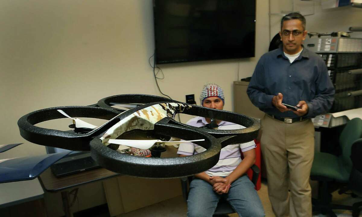 Prasanna Kolar, right, controls a quad copter through an app on his smart phone. Kolar and other students at UTSA's Electrical and Computer Engineering Department are studying how to control a drone with brain waves collected by the electroencephalogram system (cap) worn by Mauricio Merino, a masters student in Electrical Engineering. A grant from the Department of Defense will enable UTSA's drone researchers to acquire two state-of-the-art systems to analyze brain waves and applying that knowledge to control drones with brain waves. Wednesday, August. 27, 2014.