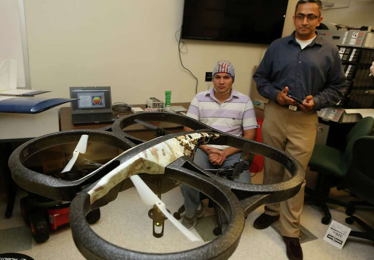 Prasanna Kolar, right, a masters student in Computer Engineering at UTSA, controls a quad copter through an app on his smart phone. Kolar and other students at UTSA's Electrical and Computer Engineering Department are studying how to control a drone with brain waves collected by the electroencephalogram system (cap) worn by Mauricio Merino, a masters student in Electrical Engineering. A grant from the Department of Defense will enable UTSA's drone researchers to acquire two state-of-the-art systems to analyze brain waves and applying that knowledge to control drones with brain waves. Wednesday, August. 27, 2014.