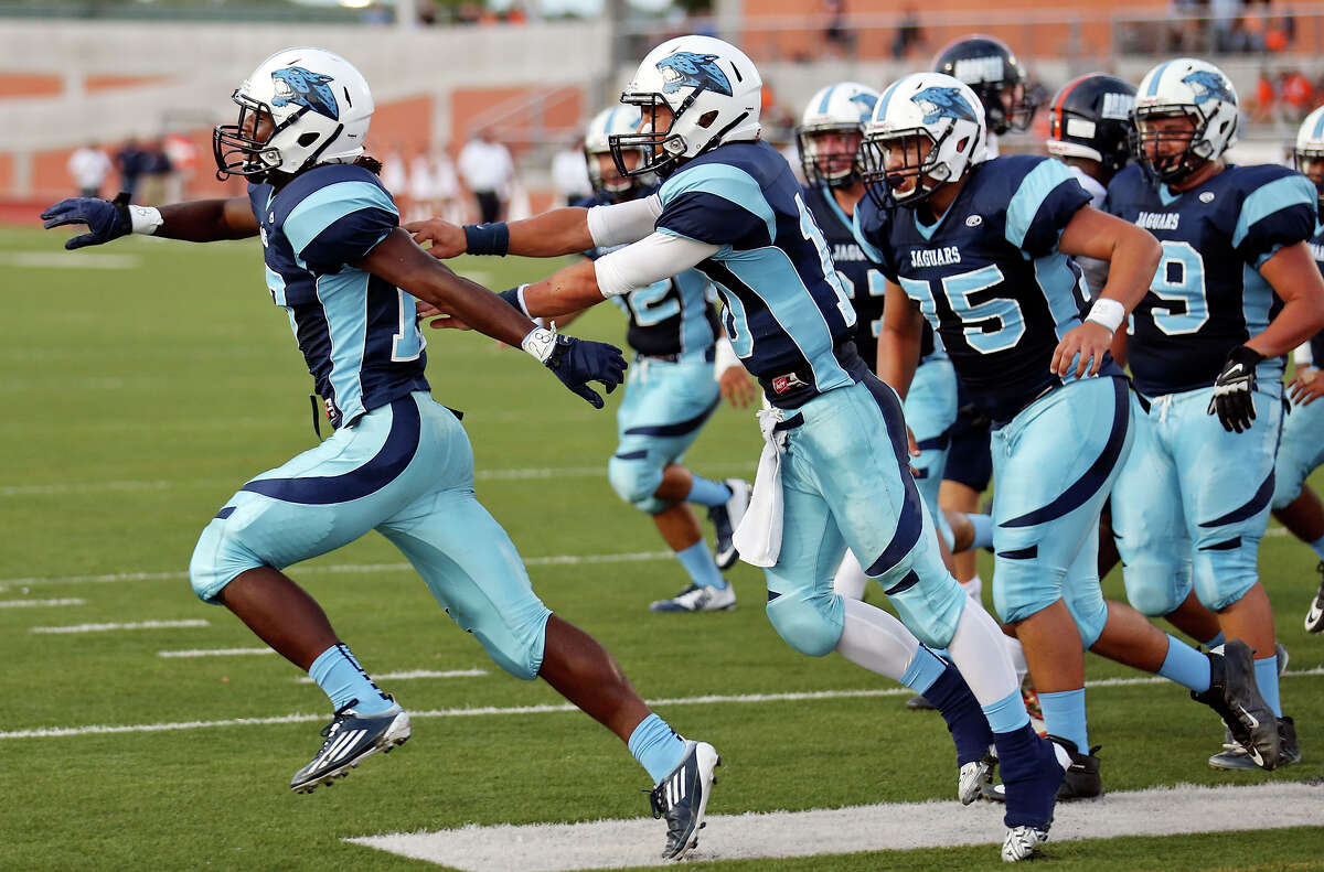 Johnson's Braedon Williams (left) celebrates with teammates after scoring a touchdown against Brandeis during first half action Friday Aug. 29, 2014 at Heroes Stadium.