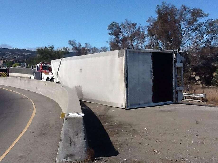 A big rig carrying books crashed onto its side Tuesday on the Highway 101 off ramp, causing a long backup near San Francisco International Airport. Photo: CHP