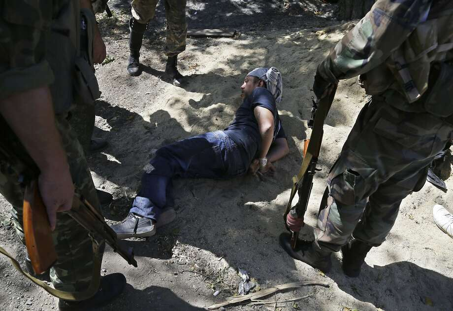 A government soldier is held by pro-Russian rebels in Novokaterynivka village in eastern Ukraine. Photo: Sergei Grits, Associated Press