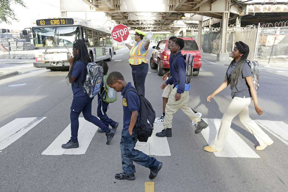 Children walk a Safe Passage route along 63rd Street as crossing guard Patricia Howard stops traffic in Chicago, which started using guards last year and is increasing their numbers. Photo: M. Spencer Green, Associated Press