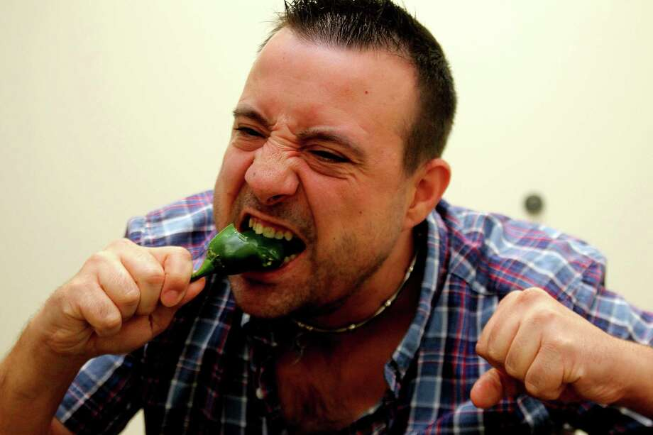 """Joseph Gilmore gobbles handfuls of jalapeños as he trains for the  jalapeño-eating contest at the Pearland International Festival. """"If they're pickled, I'll just call it now. I won,"""" says Gilmore, who is  a drafter for a surveying company. Photo: Pin Lim, Freelance / Copyright Pin Lim."""