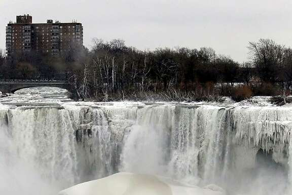"FILE - This Jan. 10, 2014 file photo shows the US side of Niagara Falls in New York beginning to thaw after  the recent ""polar vortex"" that affected millions in the US and Canada. Remember the polar vortex, the huge mass of Arctic air that can plunge much of the U.S. into the deep freeze? You might have to get used to it. we should see more of these in the future because a study partially links these polar vortex related cold outbreaks to loss of sea ice off Russia as the world gets warmer. But we have to note that last year's polar vortex chill was slightly different and not connected to sea ice loss, researchers say. (AP Photo/Nick LoVerde, File)"