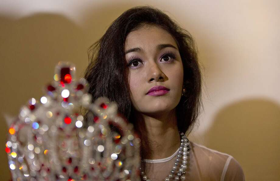 Royally miffed:At a press conference in Yangon, May Myat Noe - Myanmar's first international   beauty queen and winner of the 2014 Miss Asia Pacific World - sits with the crown that she has   been accused of stealing. The dethroned queen said she won't return the crown, valued at   $100,000, until the pageant's organizers apologize for calling her a liar and a thief. Photo: Gemunu Amarasinghe, Associated Press