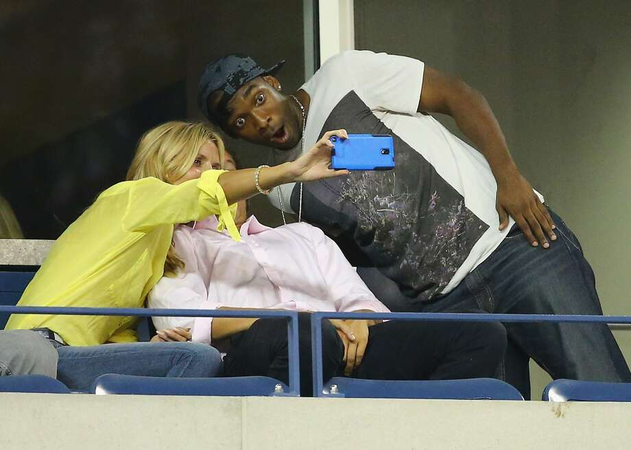 Please, I'm trying to watch the tennis: Comedian Jay Pharoh and model Heidi Klum pose for a selfie with an unidentified person at the U.S. Open in New York. Photo: Al Bello, Getty Images
