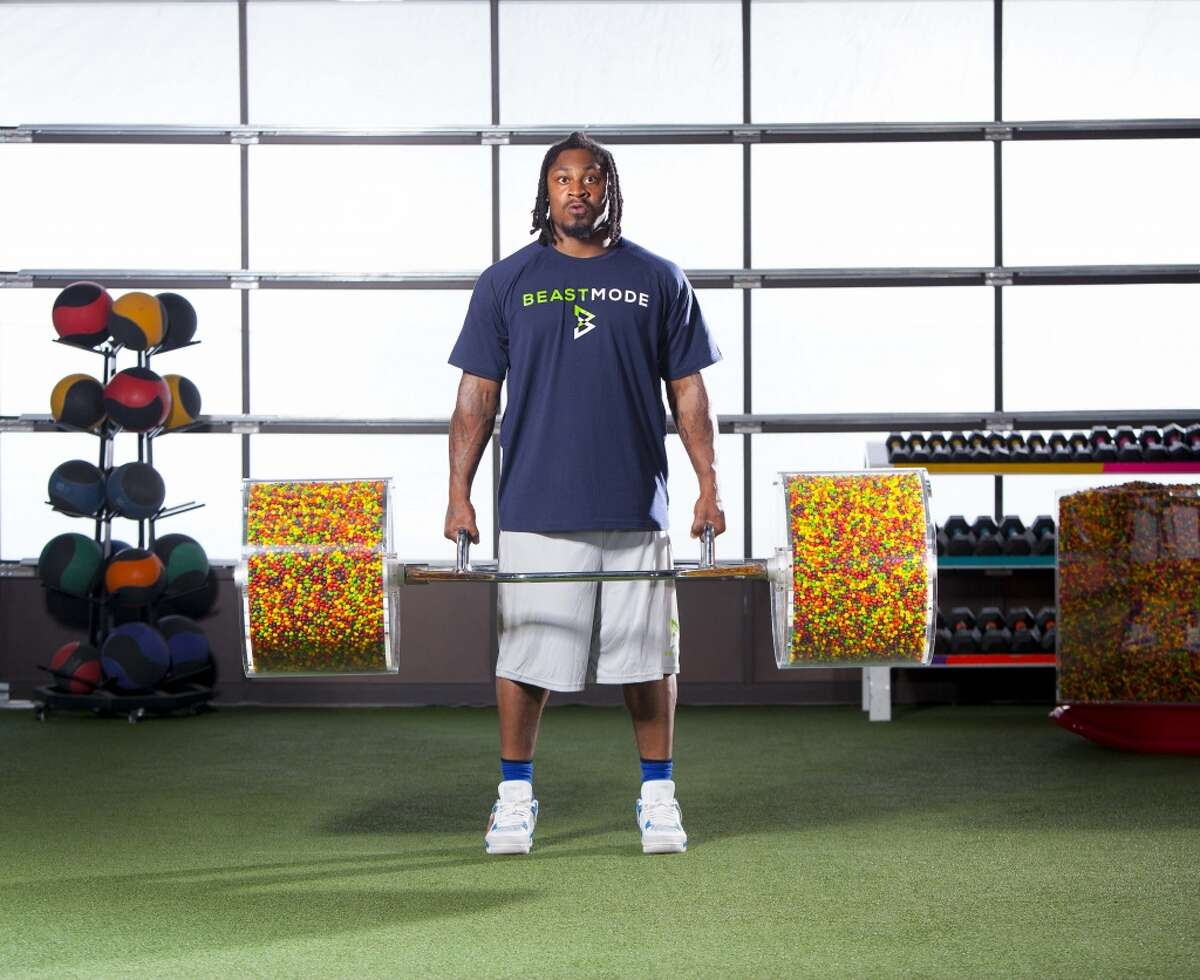 Marshawn Lynch has taken part in ads for Skittles over the years. Here, he lifts a barbell filled with Skittles during a commercial shoot for the candy brand.