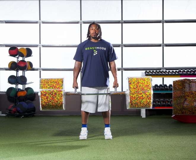 Marshawn Lynch lifts a barbell filled with Skittles during ...