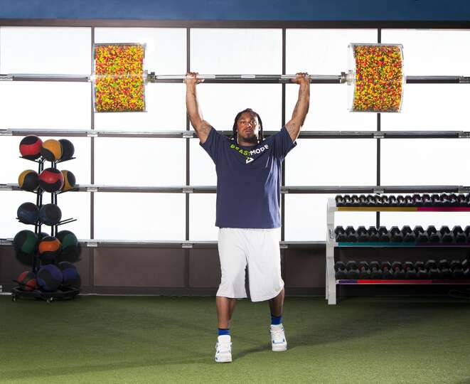 Marshawn Lynch lifts a barbell filled with Skittles above ...