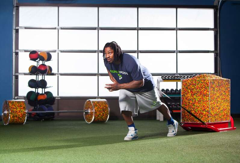 Marshawn Lynch pulls a training sled filled with Skittles ...