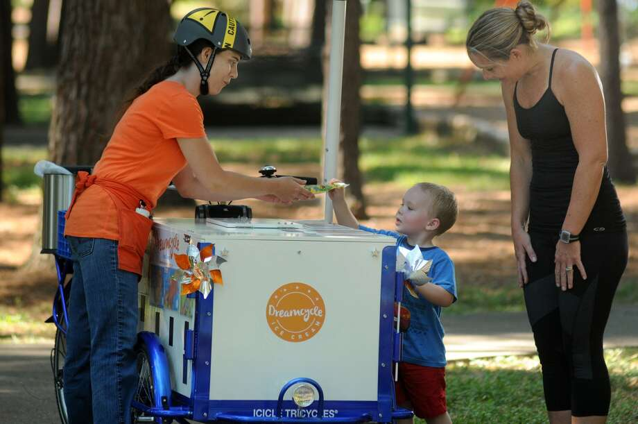 Sara West, left, serves customer Caleb Churchill, 2, who was with his mom, Sherri, duing a stop on West's Dreamcycle at Rustling Elms Park in Kingwood. Photo: Jerry Baker, Freelance
