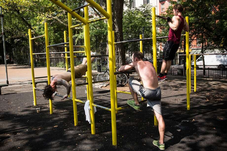 NEW YORK, NY - SEPTEMBER 02:  Men excercise on bars in Tompkin Square Park on September 2, 2014 in New York City. After an unusually cool summer, temperatures are supposed to hit the high 80s this week.  (Photo by Andrew Burton/Getty Images) Photo: Andrew Burton, Getty Images