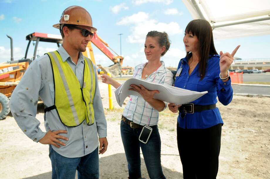 Gemma Leija, right, the unit director of the H-E-B, talks to Samantha Benson, field office manager for Williams Brothers Construction and James Spofford, supervisor of Petroleum Solution Inc., on the site of the supermarket on League City Parkway. Photo: Jerry Baker, Freelance