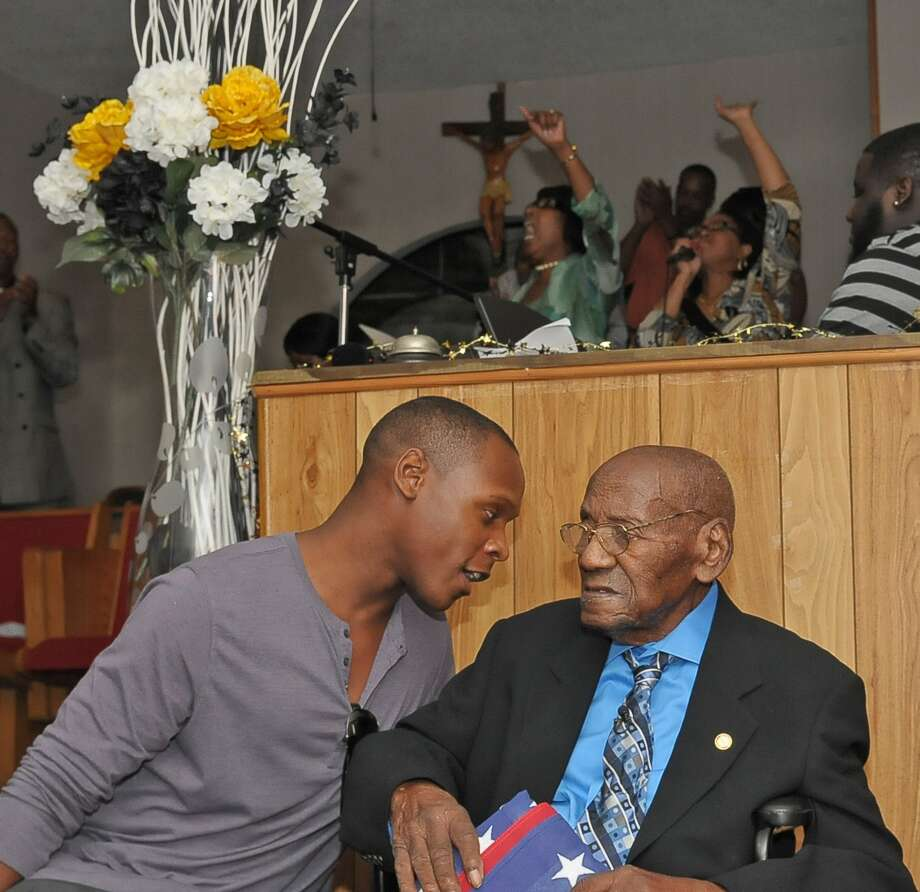 Samuel Roberts talks with his father James Roberts as the choir sings in the background during James'  100th birthday celebration at St. James Missionary Baptist Church in July. Photo: Copyright Tony Bullard 2014, Freelance Photographer / Copyright 2014 Tony Bullard & the Houston Chronicle
