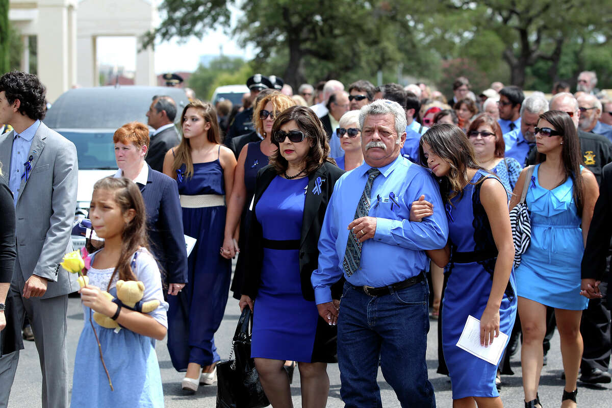 Mourners walk to the rendering of honor ceremonies outside the Cornerstone Church during funeral services for Elmendorf Police Chief Michael A. Pimentel on September 2, 2014.